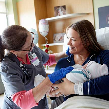 nurse with new parents and baby